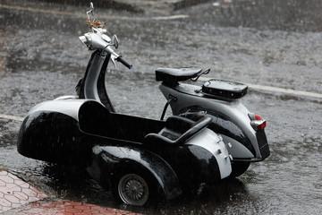 Motorrad mit Beiwagen im Platzregen auf Bali
