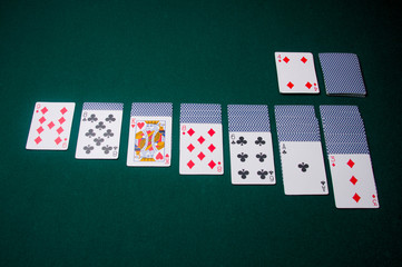 Playing cards are set up for a game of solitaire, on green felt