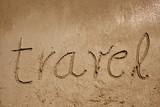 Travel handwritten in sand on a beach poster