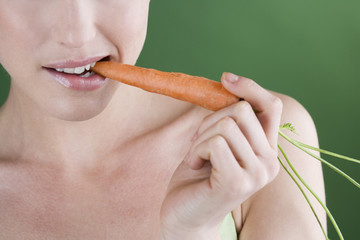 A young woman eating a carrot, close-up