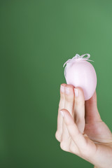 A woman holding a pink Easter egg, close-up