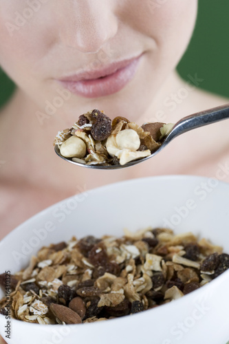 A young woman eating a bowl of muesli, close-up
