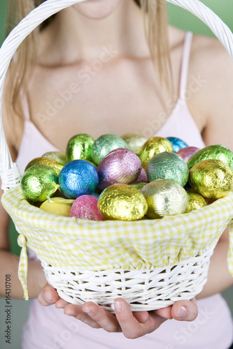 A young woman holding a basket full of Easter eggs