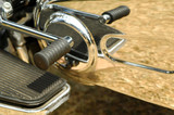 motorcycle gearshift and foot-plate reflections in chrome
