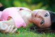 Busty young girl laying lays down on a meadow in grass