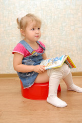 Little girl sitting on red potty with open book