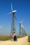 Girl driving bicycle on the road in wind farm. poster