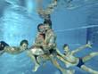 Umarmung der Eltern mit zwei söhnen unter Wasser