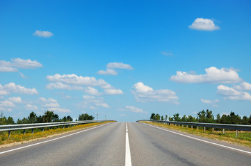 Empty countryside road leading straight to cloudy blue sky