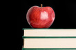 A red apple red on a green book