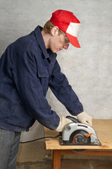 The worker operates circular saw