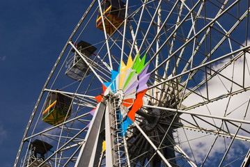 Attraction is the Ferris wheel on background blue sky