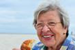 Seniorin isst Croissant am Strand
