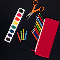 Child's school art supplies on black background