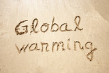 Global warming handwritten in sand for tourism poster