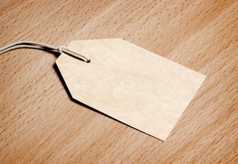 Blank tag on wooden background.