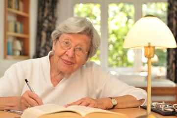 Seniorin am Schreibtisch mit Buch und Stift II