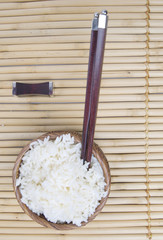 bowl of rice with oriental sticks over bamboo