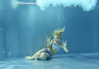 Freches Mädchen zeigt Zunge und Viktory-Zeichen unter Wasser