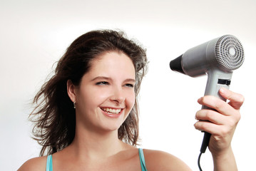 Pretty woman drying her hair with dryer