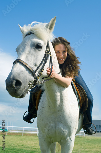smiling girl embraces a white horse