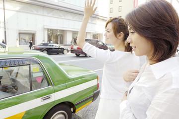 タクシーを停める女性