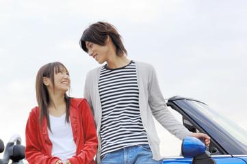 オープンカーにもたれながら会話するカップル