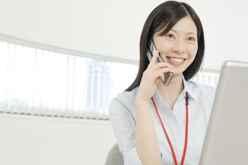 パソコンを見ながら携帯電話で会話をする女性