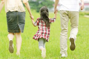 両親と手をつないで歩く女の子の後姿