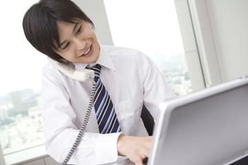 電話をかけながらパソコンを打つビジネスマン