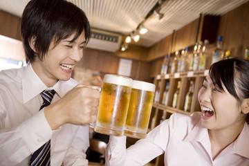 ビールで乾杯するビジネスマンとビジネスレディ