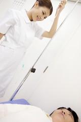 ベッドで横になる患者と点滴を準備する看護師