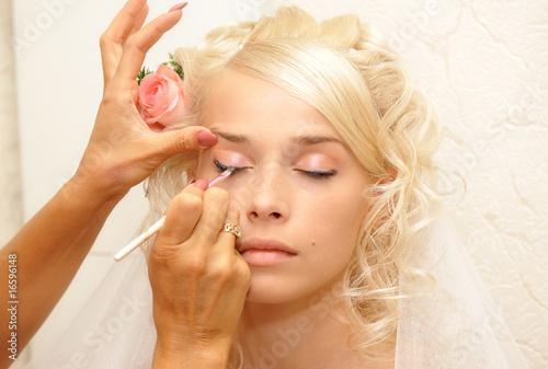 Młoda panna młoda robi makijaż