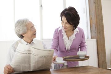 新聞を読んでいる夫にコーヒーを用意している妻