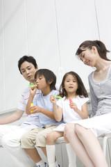 しゃぼん玉で遊ぶ子供達と見守る両親