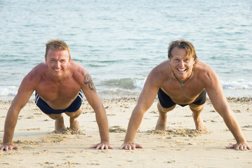 Two happy smiling men exercising on the beach.