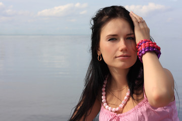 Dark-haired girl in pink sleeveless shirt against water and sky