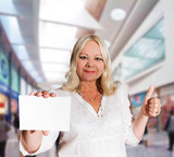 mature woman with business card in hand poster