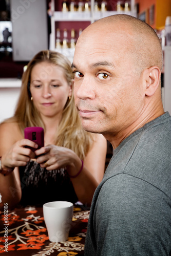 Bored man with woman on cell phone