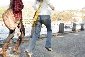 湖畔を走る女性2人の足元