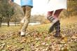 落ち葉の上を走るカップルの足元