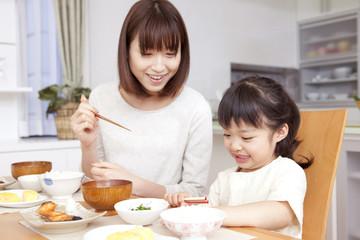 お箸の使い方を教える母親とそれを聞く娘