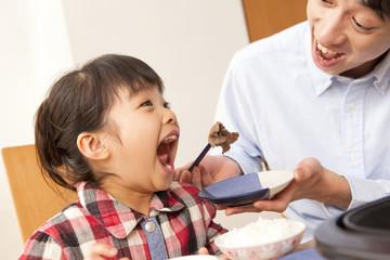 娘に肉を食べさせる父親