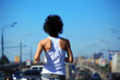 girl goes on road among cars,  rear view on belt