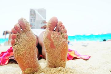 leggere sulla spiaggia con piedi sulla sabbia