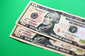 two 10 dollars banknote on the green background