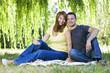 Portrait of cheerful couple sitting on the grass
