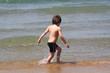 petit garçon qui marche au bord de l'eau