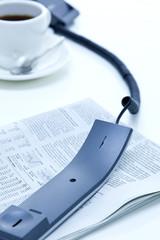 新聞紙の上に置かれた受話器