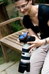 junge Frau mit Kamera und Schmetterling darauf